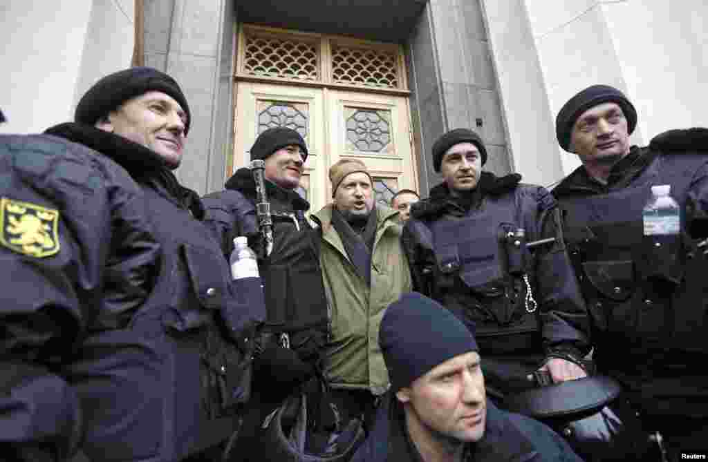 Newly-elected speaker of parliament Oleksandr Turchynov poses for a picture with a group of antigovernment protesters outside the Ukrainian parliament building.