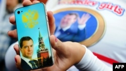 Сторонница Дмитрия Медведева показывает телефон iPhone 4 с его фотографией во время акции на Красной площади. Москва, 14 сентября 2011 года.