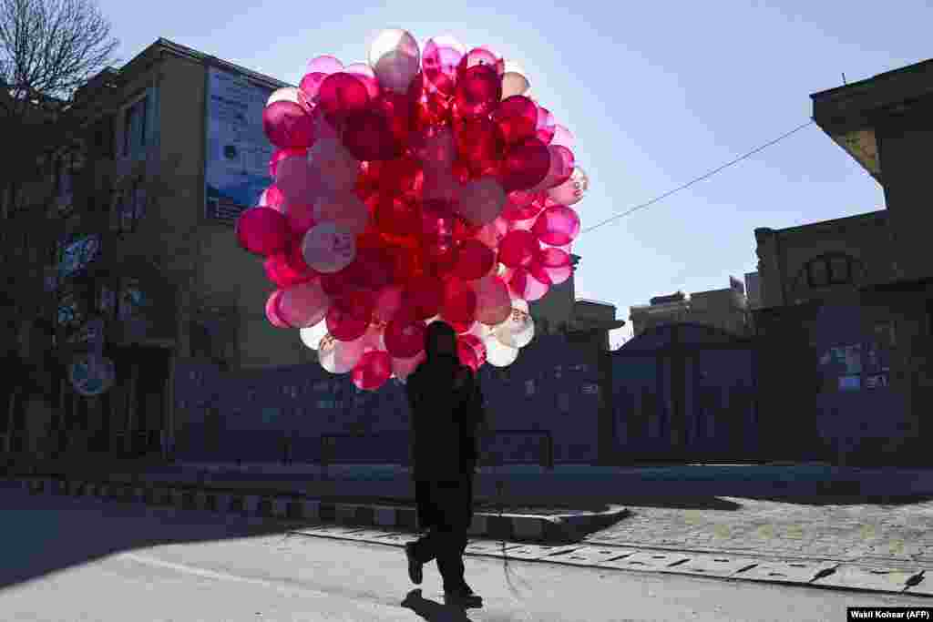 An Afghan vendor selling balloons looks for customers along a street in Kabul on Valentine's Day. (AFP/Wakil Kohsar)