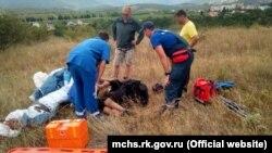 Спасатели и медики оказывают помощь парапланеристу