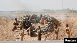 Kurdish Peshmerga forces clash with Islamic State militants in the town of Daquq, south of Kirkuk, on September 30.