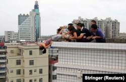 Rescuers and relatives grapple with a woman attempting to leap to her death in Zhanjiang, China, in 2012. They saved her. Photo by Reuters/Stringer