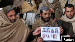 Afghan villagers show a picture of nine men during a protest last month against U.S. Special Forces accused of overseeing torture and killings in Wardak Province.