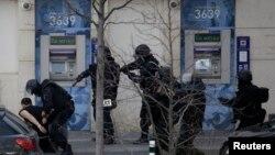 Полиция задерживает мужчину, который захватил в заложники двух человек в почтовом отделении в пригороде Парижа Коломб. 16 января 2015 года.