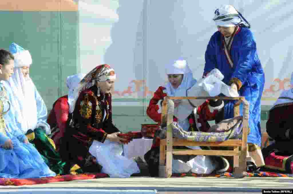 На сцене показывают обычай укладывания младенца в колыбель.