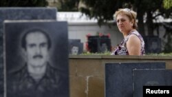Azerbaijan -- A woman walks past tombstones with portraits of Azeris killed during the fighting between Karabakh and Azerbaijan forces in 1993 in the Alley of Martyrs memorial cemetery in Baku, 08Sep2012