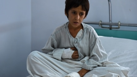 A wounded Afghan boy, a survivor of the U.S. air strikes on the MSF hospital in Kunduz, sits on his bed at a hospital in Kabul run by the Italian aid organization known as Emergency.