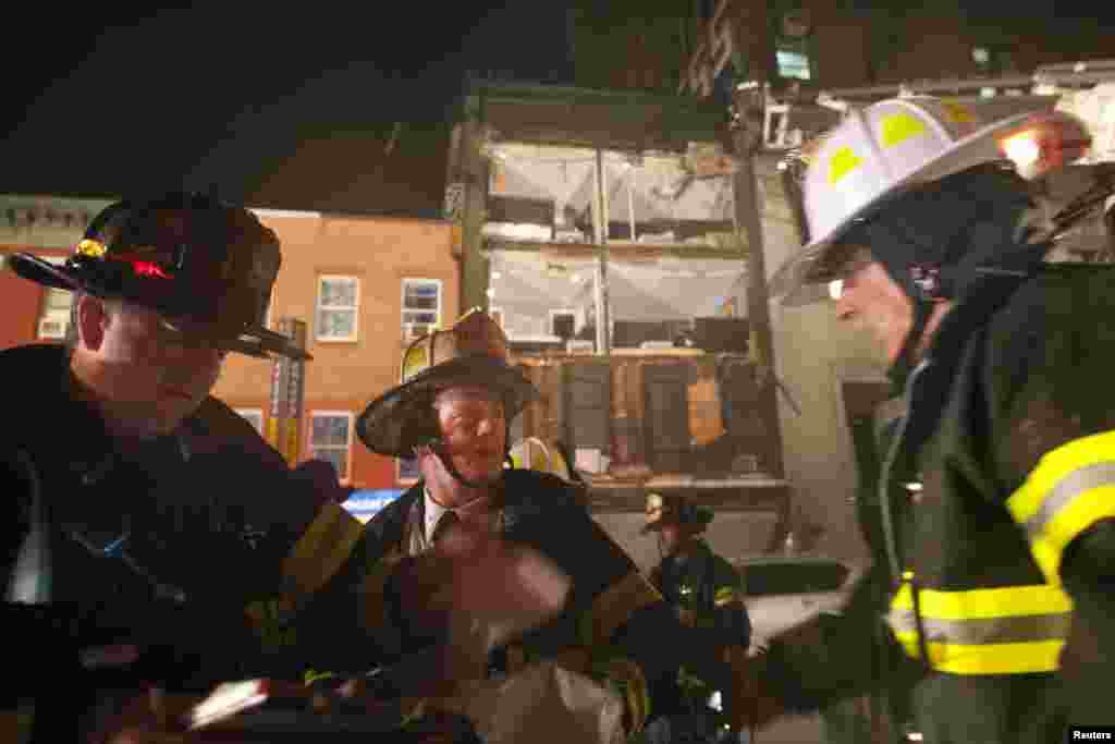 Firefighters work in front of a partially collapsed four-story apartment building in Manhattan.