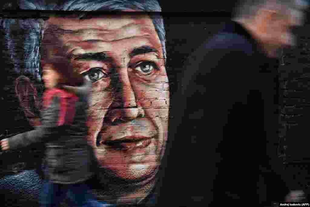 Кісі қолынан қаза тапқан серб саясаткері Оливер Ивановичтің суреті бейнеленген фреска жанынан адамдар өтіп барады. Саясаткерді 2018 жылы 16 қаңтарда қарулы топ кеңсе алдында атып кеткен.