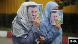 Two women cover their faces with images of Mahmud Ahmadinejad. (file photo)