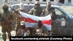 Українські солдати з білоруським національним прапором на тлі автомобіля, придбаного коштом волонтерів