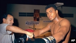U.S. -- In this February 1967, file photo, Muhammad Ali gets his gloves laced by trainer Angelo Dundee while training in Houston, Texas, for a title fight against Ernie Terrell.