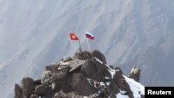 Российский и кыргызский флаги на вершине горы в Тянь-Шане, Кыргызстан. 17 сентября 2012 года.