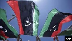 مخالفان حکومت معمر قذافی پرچم سابق لیبی را تکان می دهند.