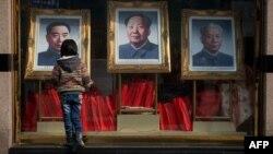 Қытайды басқарған Чжоу Эньлай, Мао Цзэдун мен Лю Шаоцидің суреттеріне қарап тұрған бала. Пекин, 26 ақпан 2013 жыл. (Көрнекі сурет)