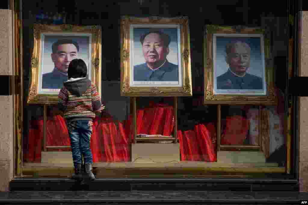"""Девочка рассматривает портреты первого премьера Госсовета КНР Чжоу Эньлая, Мао Цзэдуна и одного из руководителей компартии, председателя КНР с 1959-го по 1968 год Лю Шаоци, репрессированного во время так называемой """"культурной революции"""""""