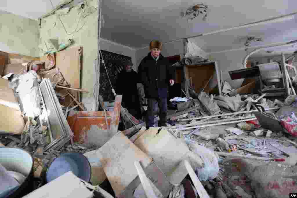 Житель Авдіївки оглядає зруйновану внаслідок нічного артилерійського обстрілу квартиру