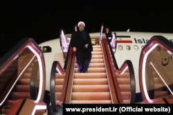 Rohani deplaning on an escalator in Tehran.