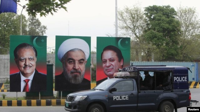A Pakistani police vehicle patrols near the portraits of the Pakistani and Iranian leaders displayed along a road during Rohani's visit.