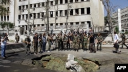 Soldiers stand at the site of twin bombings near the headquarters of the armed forces general staff in Damascus on September 26.