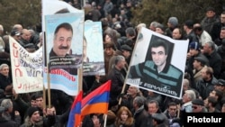 Demonstrators hold up pictures of jailed opposition members Aram Bareghamian (right) and Sasun Mikaelian at a rally on March 1.