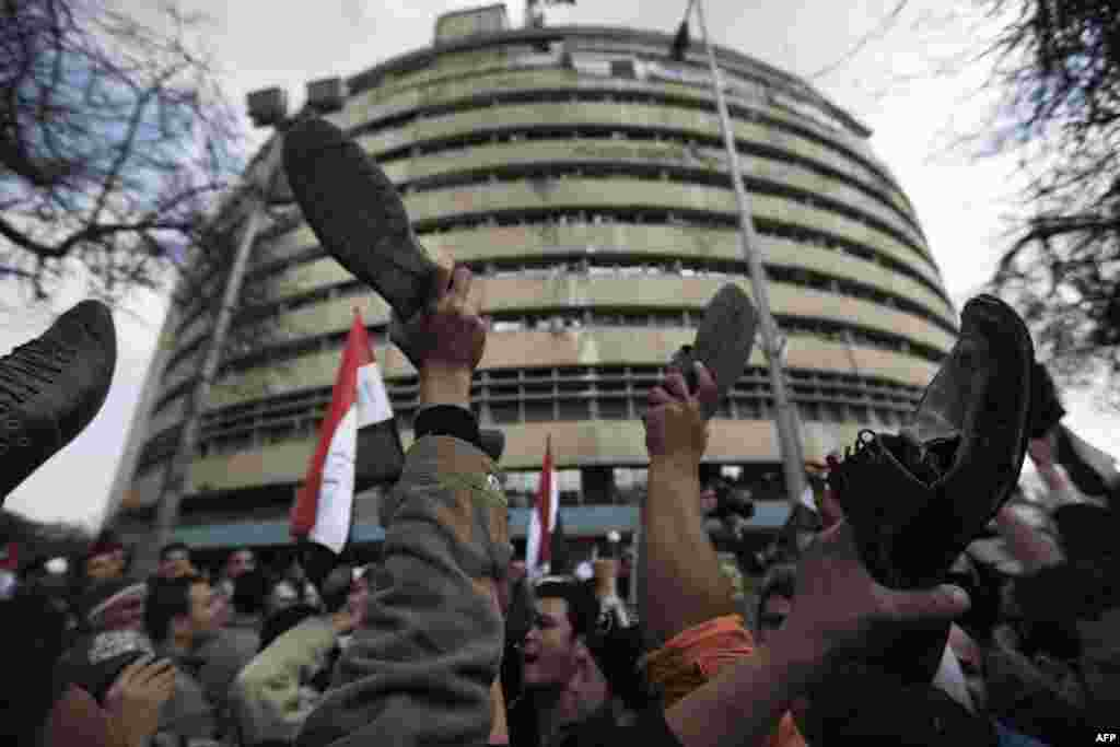 Protesters demonstrate by raising their shoes in front of the Egyptian national TV building in Cairo on February 11, 2011.