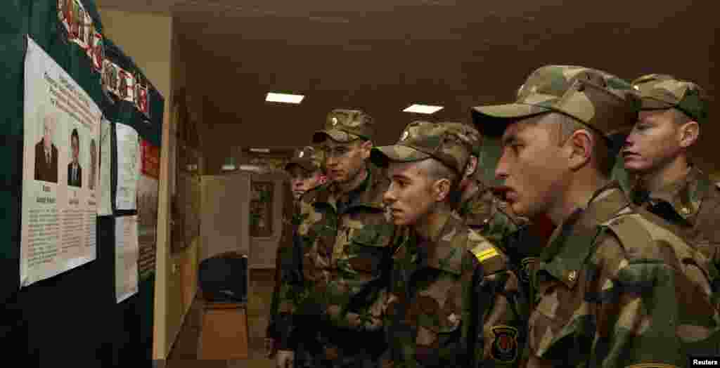 Soldiers read information about the candidates at a polling station in Minsk.
