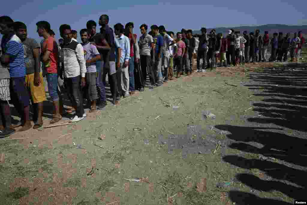 Migrants line up to receive sandwiches offered by volunteers outside a derelict hotel on the Greek island of Kos on August 17. (Reuters/​Alkis Konstantinidis)