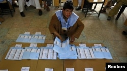 An election worker counts ballot papers at a polling station in Kandahar Province on September 18.