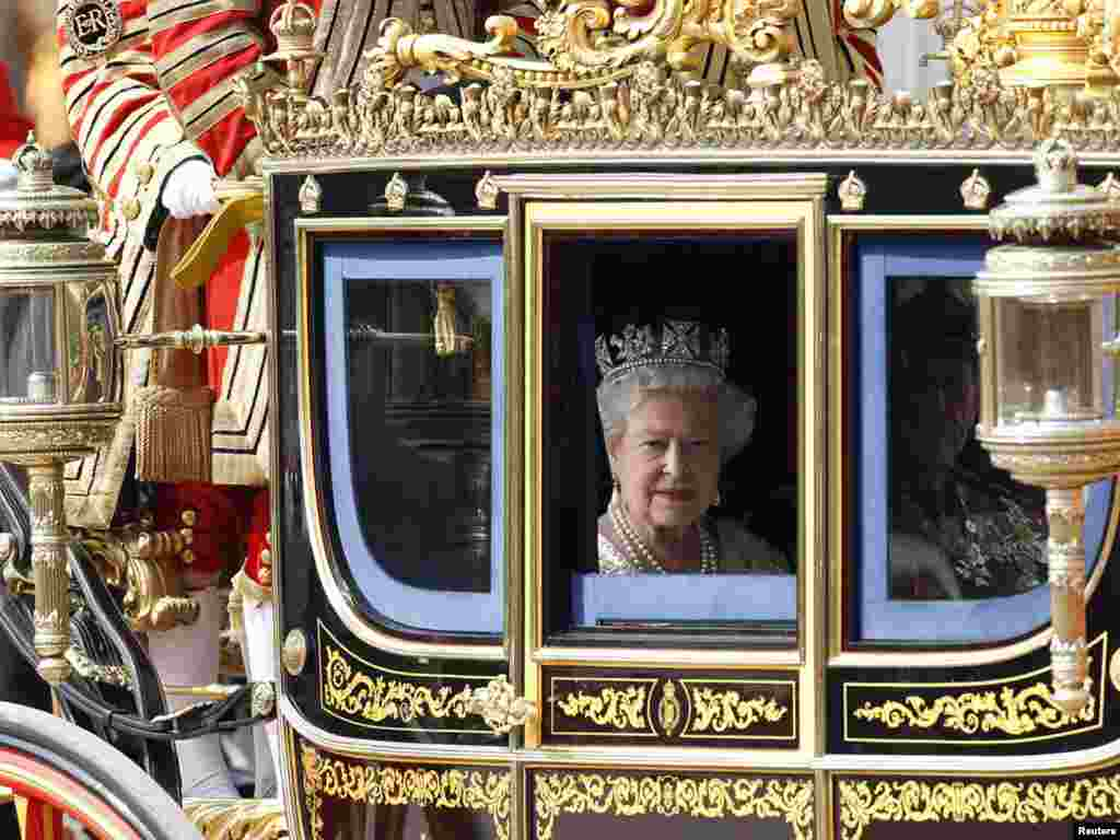The queen leaves Buckingham Palace in a horse-drawn carriage to attend the State Opening of Parliament in May 2010.