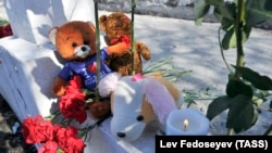 Люди несут свечи и игрушки в память о погибших в трагедии