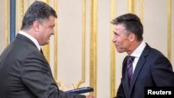 Ukrainian President Petro Poroshenko (left) greets NATO Secretary-General Anders Fogh Rasmussen during their meeting in Kyiv on August 7.