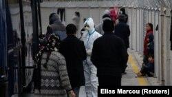 Zdravstveni radnik sa migrantima koji su stigli prethodnih dana nakon prelaska dijela Egejskog mora iz Turske u Grčku, dok čekaju postupak identifikacije prije prelaska na kopno na plovilu grčke mornarice, iz luke Mytilene, na ostrvo Lezbos, Grčka, 5. marta 2020.