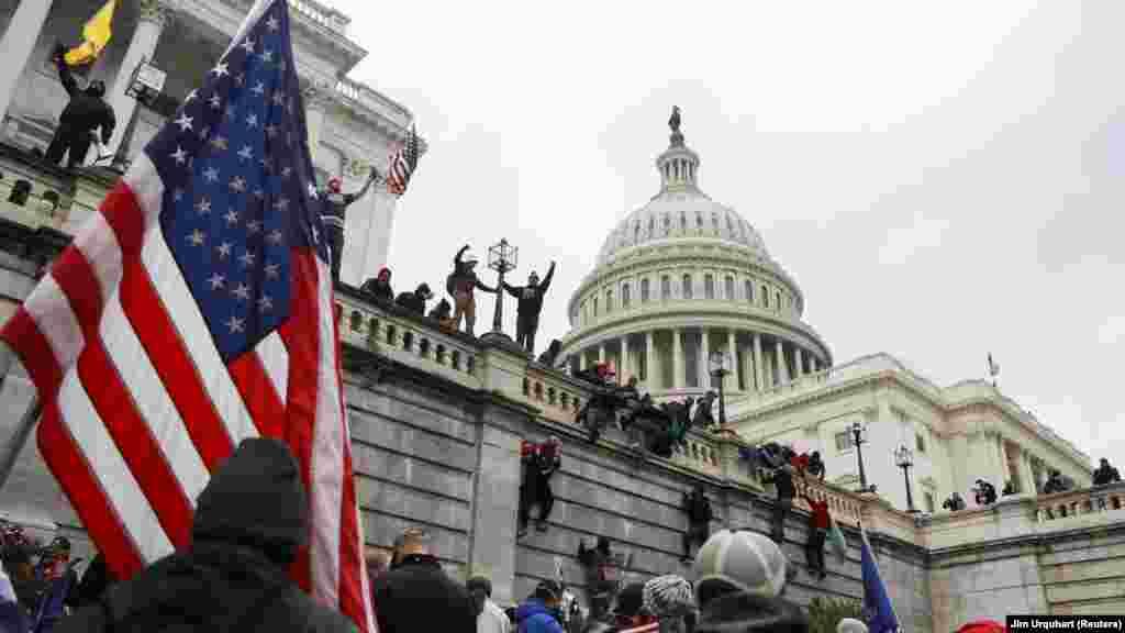 Сторонники Дональда Трампа взбираются на стены Капитолия во время акции протеста против утверждения Конгрессом США результатов президентских выборов.