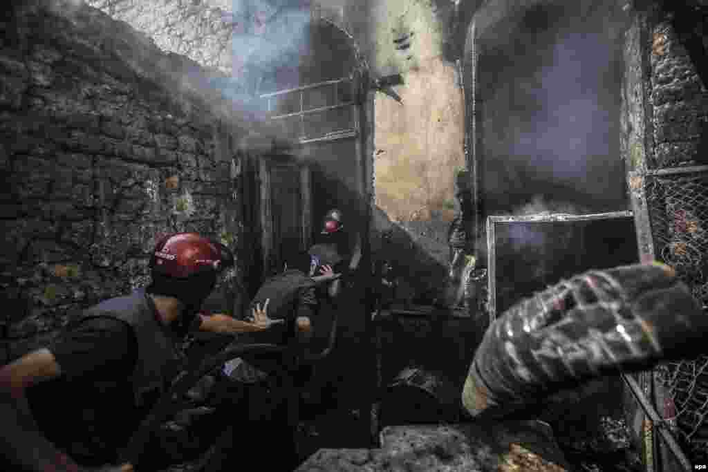Firefighters extinguish a blaze following an air strike by forces loyal to the Syrian government in the rebel-held area of Douma on the outskirts of Damascus. (epa/Mohammed Badra)