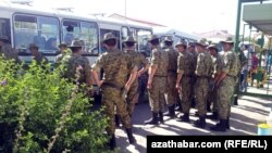 Türkmen esgerleri awtobusa münmek üçin nobata durlar.