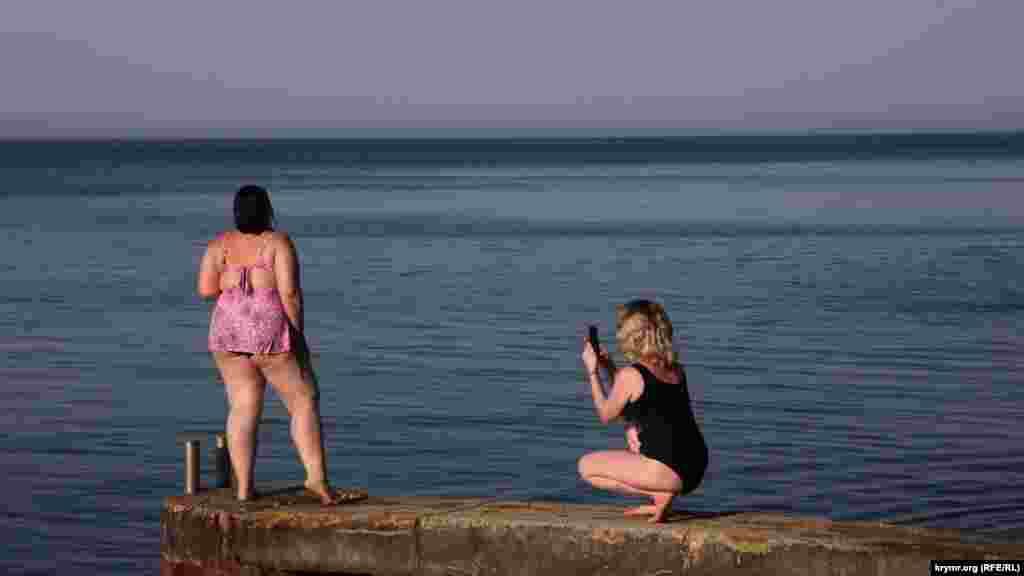 Девушки фотографируются на фоне водной глади