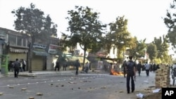 A motorbike is set on fire by protesters and rocks remain on the street during a protest in the northwestern city of Orumieh (Urmia) on August 27.