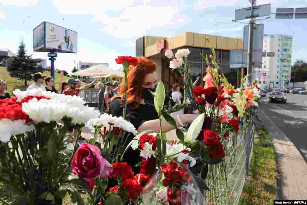 A woman places flowers at the site where the Belarusian protester died in Minsk.