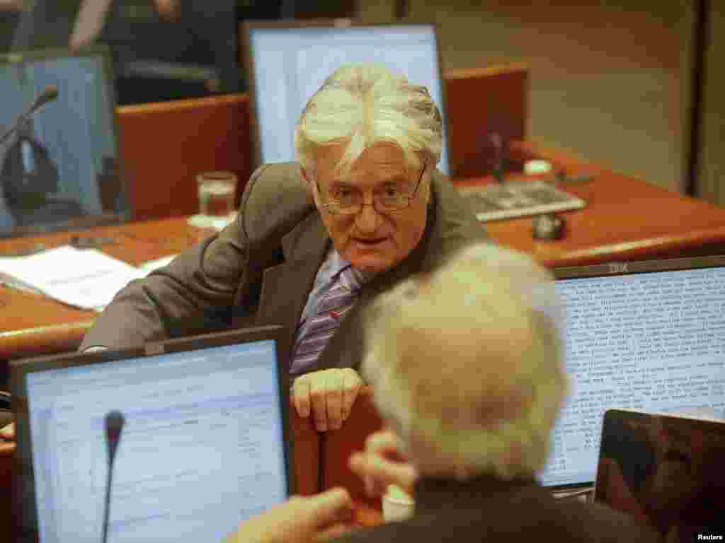 Former Bosnian Serb leader Radovan Karadzic talks to his defense team in a courtroom at the ICTY.