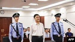 Бывший председатель регионального правительства Синьцзян-Уйгурского автономного района (СУАР) Нур Бекри (в центре) в суде по его делу на датируемом 25 июля 2019 года кадре, которое опубликовал Промежуточный народный суд китайского города Шэньян. Фото предоставлено агентством AFP.