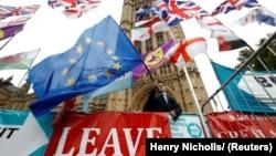 Un protestatar anti-Brexit, fluturând un steag al UE, alături de o pancardă pro-Brexit. Imagine de la finalul lunii octombrie, în fața Palatului Westminster