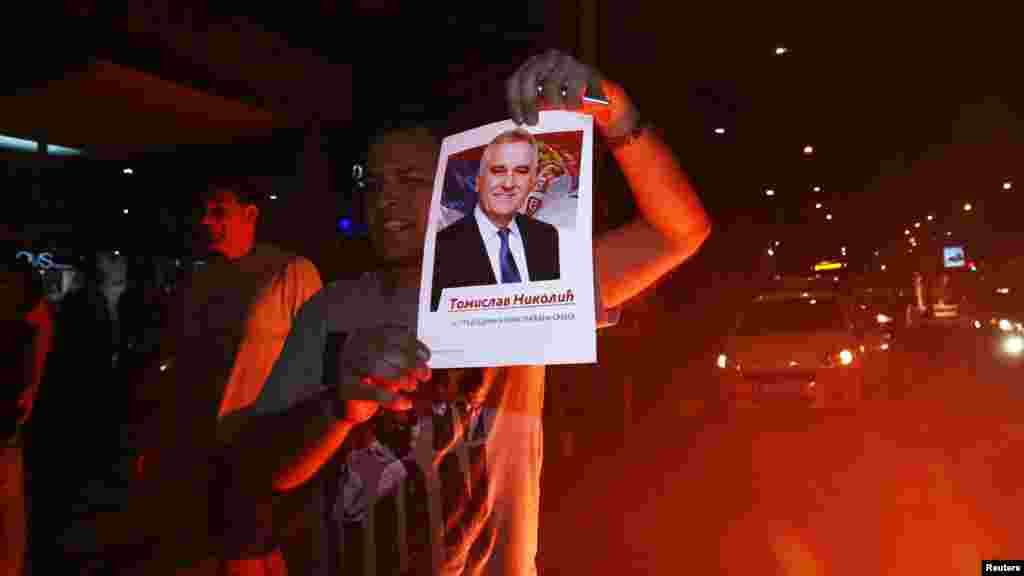 A supporter of the nationalist Serbian Progressive Party (SNS) celebrates Tomislav Nikolic's victory in a presidential election in Belgrade on May 20. (Reuters/Djorde Kojadinovic)