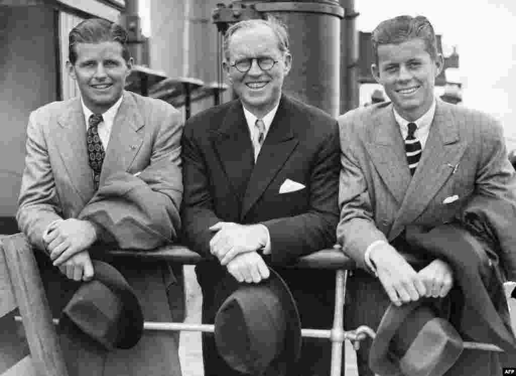 "JFK (right) and his older brother, Joseph P. Kennedy, Jr. (left), beside their father, Joseph, in Southampton, England on the deck of French ""Normandy"" cruiser liner after their arrival from the United States on July 2, 1938. Joseph was later killed in action, in 1944, during World War II."