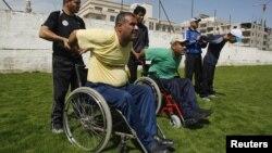 Палестиналық паралимпиадашы Хамис Закот (сол жақта) басқа да мүмкіндігі шектеулі спортшылармен бірге жаттығады. Газа қаласы, 28 мамыр 2012 жыл. (Көрнекі сурет)