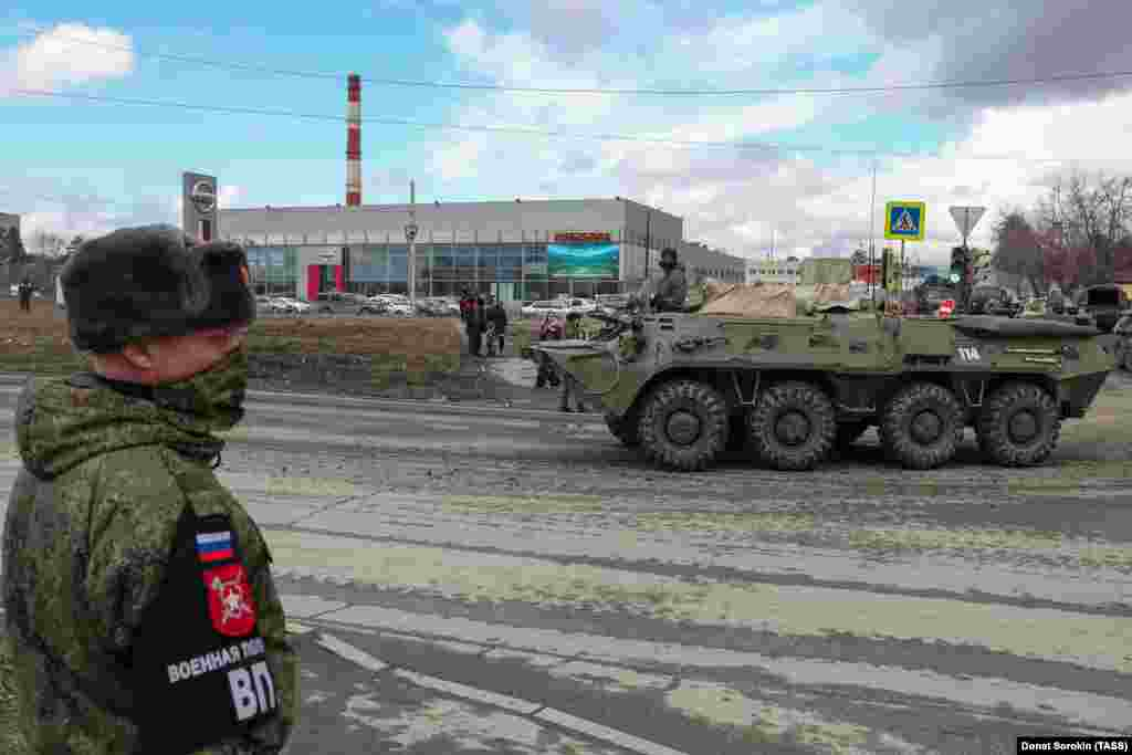 A masked soldier watches a BMP-3 infantry fighting vehicle passing by.
