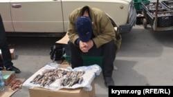 Балық сатып отырған адам. Керчь, 2014 жылдың шілдесі.