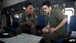 A picture taken on March 15 shows a Royal Malaysian Air Force navigator explaning to an AFP reporter aboard a Malaysian Air Force CN235 during a search and rescue (SAR) operation for Malaysia Airlines Flight 370.