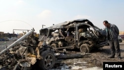 A resident stands near burned vehicles after a car-bomb attack in Baghdad's Kadhimiyah district on February 8.
