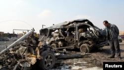Mbetjet e makinës së djegur në lagjen Kadhimiya, pas sulmit me makinë-bombë